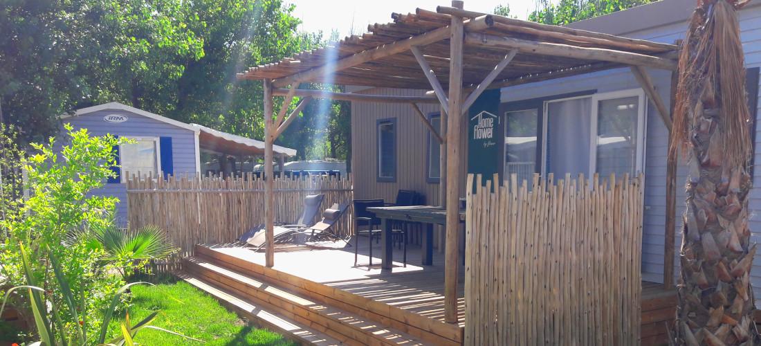 pergola en bois posé sur une terrasse en pin par l'entreprise occia dans un camping a marseillan plage