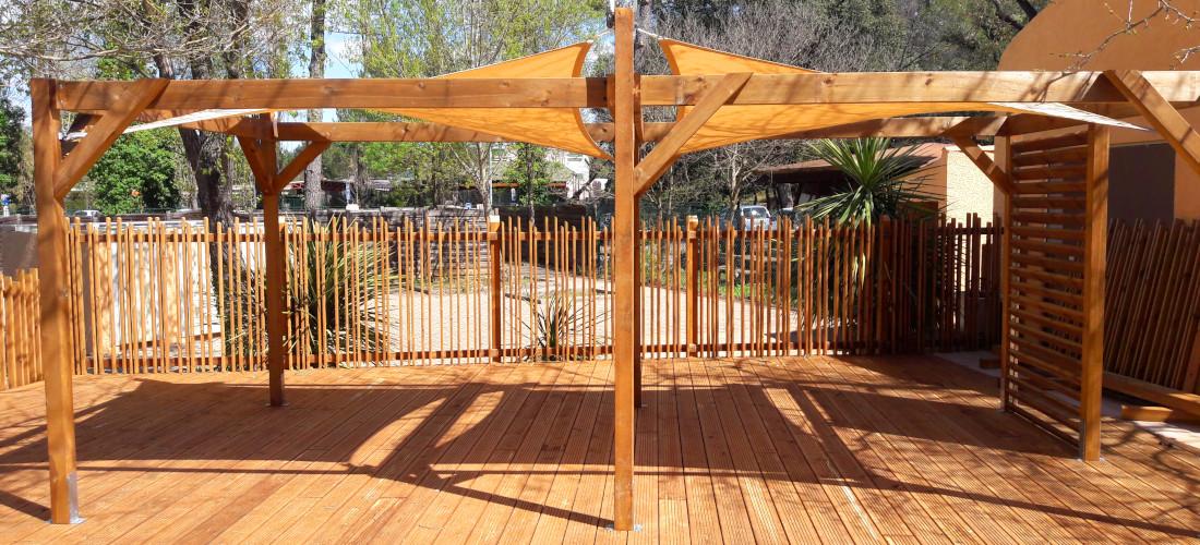 pergola en toile posé surt une terrasse en bois avec des barrières bois design dans un restaurant de plage a vias