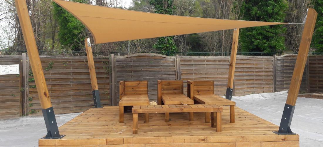 pergola en kit posée sur une terrasse en pin dans un camping posé par occia conception bois a agde